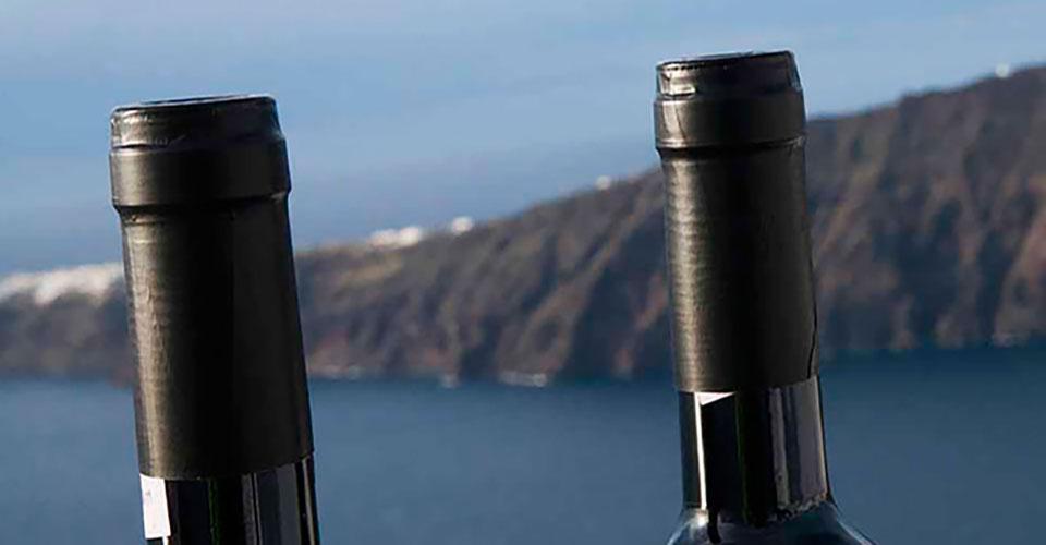 Δύο φιάλες κρασιού με θέα την καλντέρα της Σαντορίνης