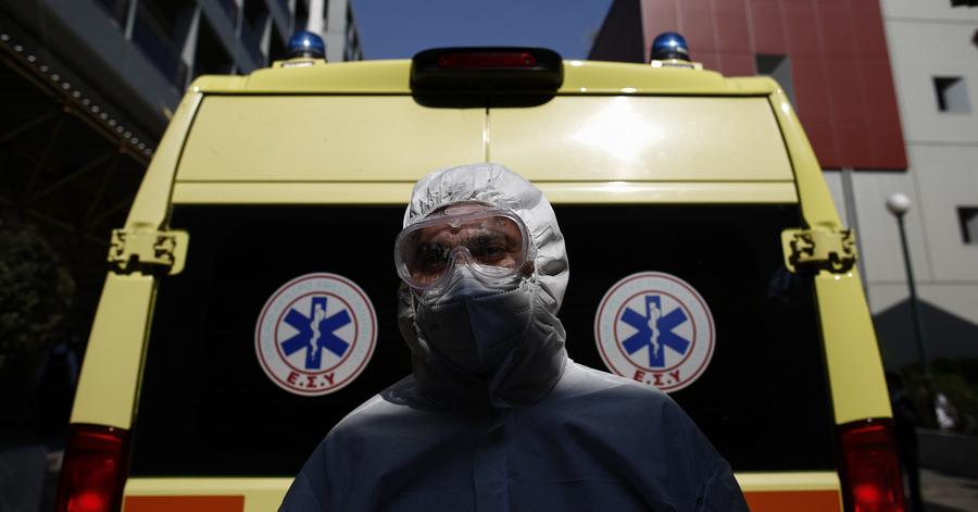 Νοσηλευτής με μαπ για covid-19 μπροστά από ασθενοφόρο