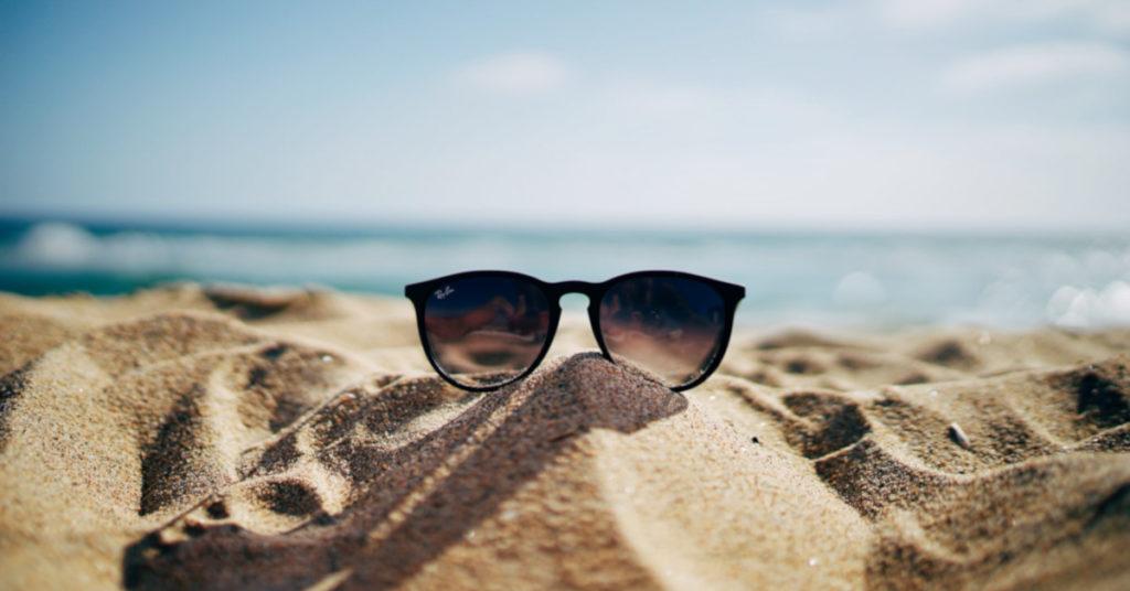 Γυαλιά ηλίου πάνω σε αμμώδη παραλία