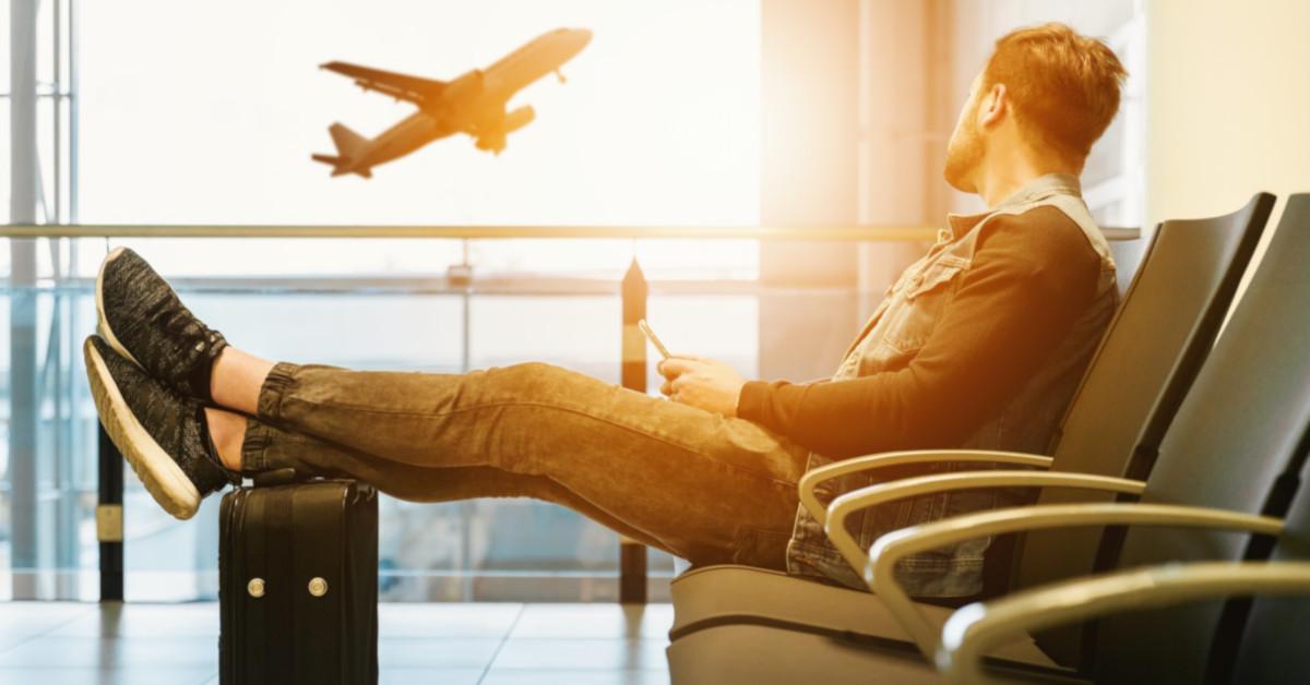 Ταξιδιώτης σε αεροδρόμιο με τα πόδια πάνω σε βαλίτσα