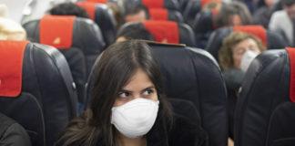 Επιβάτης σε αεροπλάνο φορώντας μάσκα προστασίας