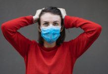Γυναίκα με μάσκα κρατάει το κεφάλι της