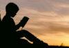 Παιδί που κάθεται και διαβάζει στο ηλιοβασίλεμα