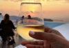 Ποτήρι κρασί με φόντο το ηλιοβασίλεμα της Σαντορίνης