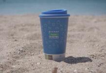 Επαναχρησιμοποιούμενο μπλε ποτήρι με καπάκι στην παραλία